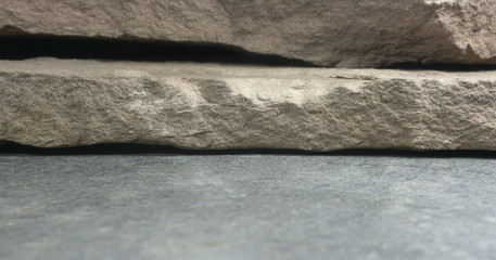 Stone board empty table in front of blurred background. Perspective brown rock over blur white background..