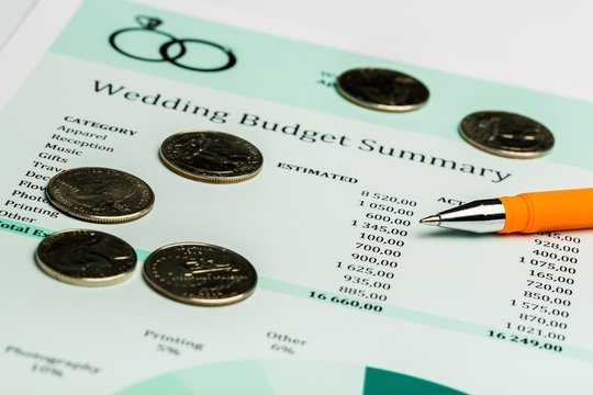 Pen and Coins on Wedding Budget Summary