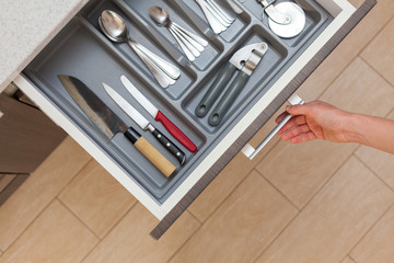 Fototapeta High angle top view cropped photo of woman hand open kitchen drawer by door handle, with different cutlery spoon, pizza knife, fork and stuff obraz