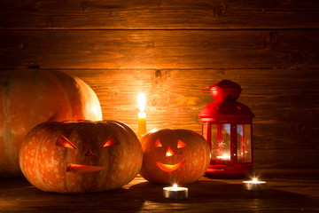 Halloween pumpkins and candles on wooden background