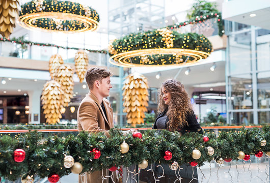 A young couple looking at each other in shopping center at Christmas.
