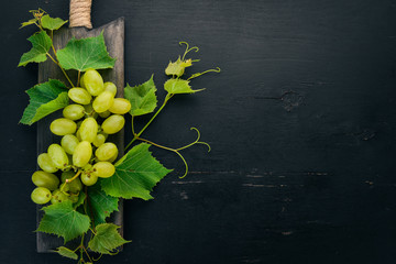 Fresh green grapes with leaves of grapes. Top view. On a black wooden background. Free space for text. Fototapete