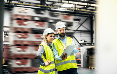 A portrait of an industrial man and woman engineer with tablet in a factory, working. Wall mural