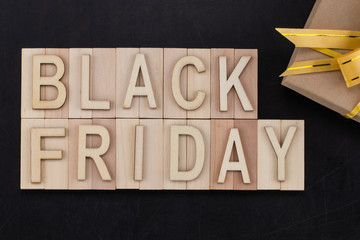 black Friday - text in wooden letters on blackBoard  with gift . Copy space