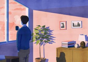 夕暮れの中の窓際の男性