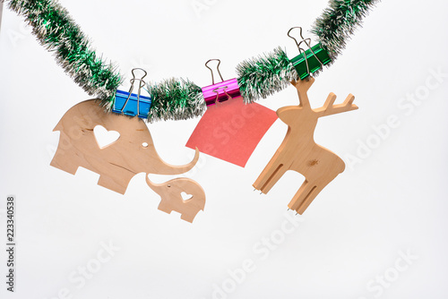 christmas decorations concept wooden deer and elephant with paper for note hang on tinsel on