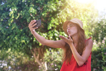 Beautiful girl in a red dress and a yellow hat, she is calling on phone with the trees in the background.