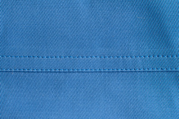 Stitches on blue fabric .