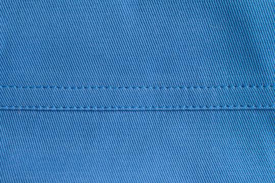 Stitches on blue fabric .