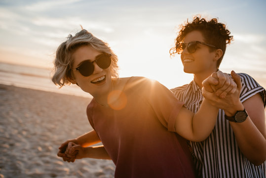 Laughing lesbian couple dancing together on a beach at sunset
