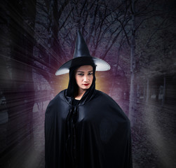 woman in Black Scary witch halloween costume with magic lights in a dark forest