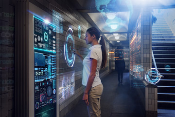 In a subway, a woman clicks on a futuristic digital platform and features futuristic graphics that can help her on her journey. Concept of: future, technology, urban