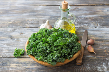 Ingredients for salad with kale, onion, garlic, olive oil on a wooden background, rustic style, horizontal