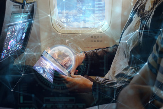 A man on plane uses the phone thanks to the wi-fi present in flight. He uses holography futuristic. Concept of: travel, vacation, technology, future.