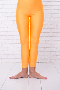 first ballet position of female feet in orange tights. leg of dancer in first position. dance class for beginner. ballet dancer practice choreo in school. graceful beauty. practicing in ballet studio.