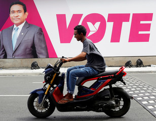 A man rides a motorcycle past an image of Maldives President Abdulla Yameen on a road ahead of the presidential election in Male