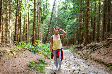 Beautiful woman smiling at path in a forest during hiking on a hill during sunrise on summer