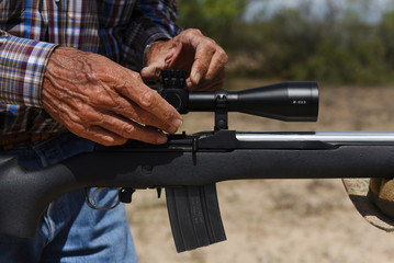 Bill Martin prepares to shoot a rifle from his gun collection on his ranch near Carizzo Springs
