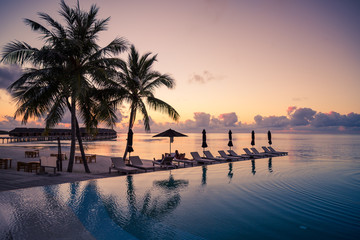 Beautiful poolside and sunset sky. Luxurious tropical beach landscape, deck chairs and loungers and water reflection. Luxurious vacation and holiday, summer beach