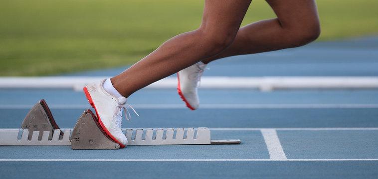 Athlete leaving starting blocks on the athletic track