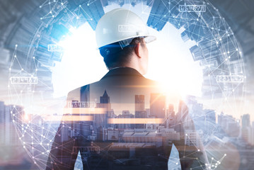 The double exposure image of the engineer standing back during sunrise overlay with cityscape image and futuristic hologram. The concept of engineering, construction, city life and future.