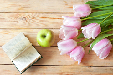 Happy teacher's day. Flowers tulips bunch with books and apple, still life
