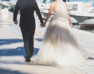 The bride and groom are walking along the embankment of the city.
