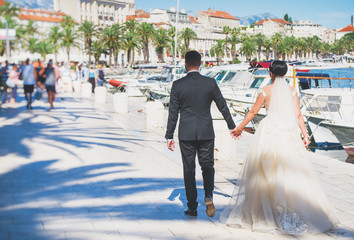 The bride and groom are walking along the embankment of the city Split.