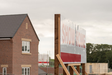 Showhome marketing sign post over new residential homes development estate in England