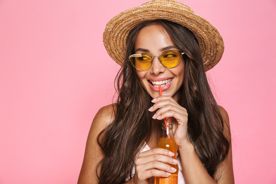 Photo closeup of european woman 20s wearing sunglasses and straw hat drinking juice from glass bottle, isolated over pink background