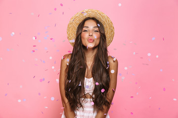 Photo of beautiful woman 20s wearing straw hat laughing while standing under confetti, isolated over pink background