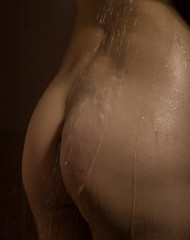 water drops run down the body. Beautiful buttocks of a nude woman with wet body, closeup on dark background