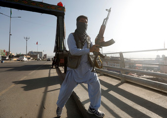 An Afghan Shi'ite armed man keeps watch at a check point in Kabul