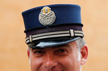 A Vatican policeman wears his hat at the Vatican