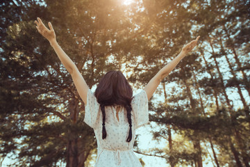 Free happy woman in forest enjoying nature. Natural beauty girl outdoor in freedom enjoyment concept. Mixed race Caucasian Asian girl posing on travel vacation holidays in dress. Back view