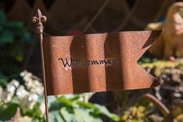 Rostiges Schild mit der Aufschrift Willkommen