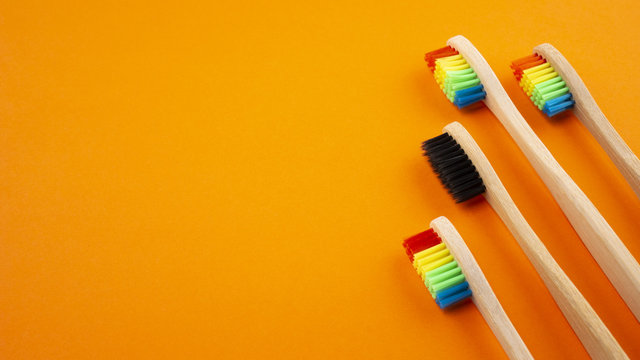 Toothbrushes on orange background on orange background. Concept of racism, social exclusion, depression or loneliness, social problems or illegal migration