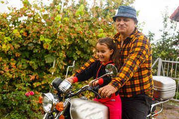 Happy grandfather and his granddaughter in handmade sidecar bike smiling motorcycle