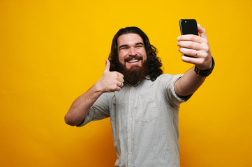 Cheerful bearded man showing thumbs up and taking selfie with smartphone over yellow background