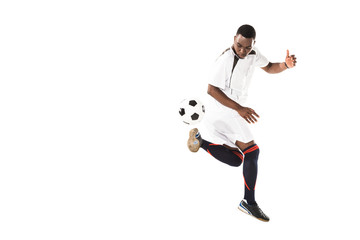 full length view of athletic african american soccer player kicking ball isolated on white