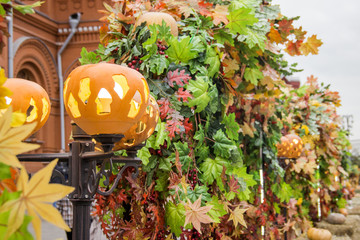 Pumpkins on the street lights. Halloween autumn decoration in a city fair