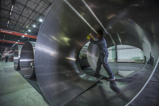 Worker examining metal in factory