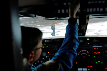 Airplane Mechanic, David Fuller, looks into the cockpit of a NASA Gulfstream III before a flight to support the Oceans Melting Greenland (OMG) research mission at an airport in Keflavik, Iceland