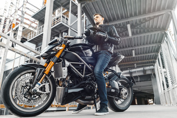 Handsome biker sitting on motorcycle and putting on helmet.