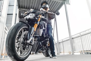 Handsome biker sitting on motorcycle and putting on helmet. Urban background, parking.