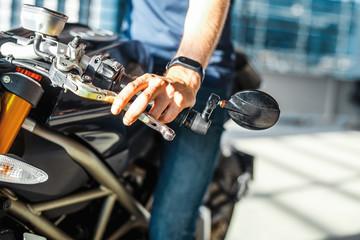 Close up of biker holding hand on handlebars at parking.