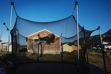A young girl plays on a trampoline taking advantage of the evening sunshine in the town of Tasiilaq, Greenland