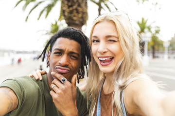 Portrait of multicultural young couple taking selfie