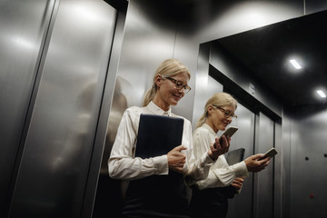 Businesswoman checking cell phone in elevator