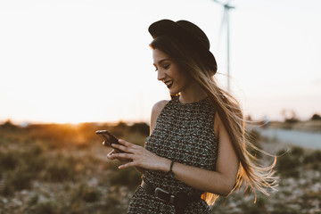 Portrait of young woman looking at cell phone by sunset